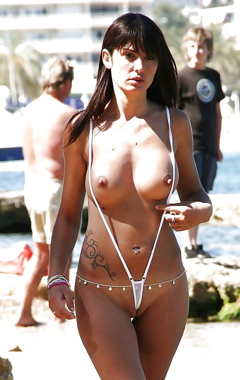 exhibitionist wears string bikini with frontal wedgie on public beach in front of families.