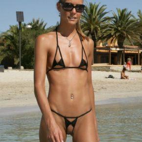 cute girl in crotchless bikini on public beach