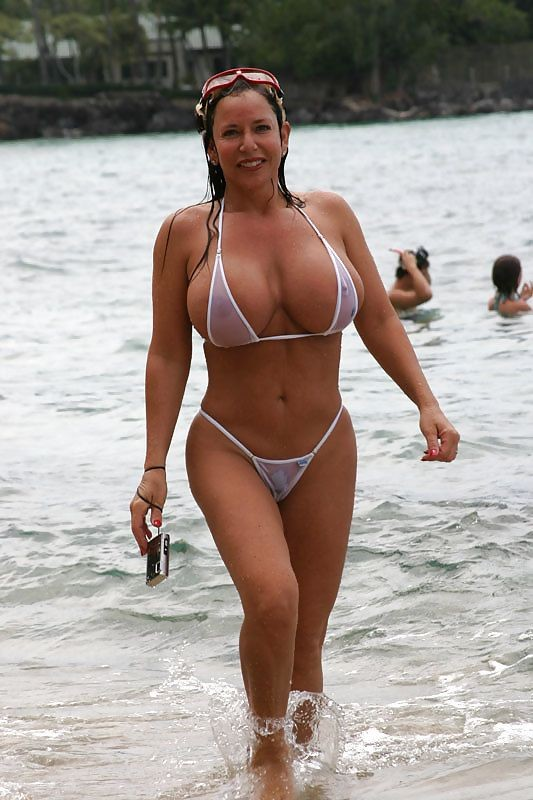 hige fake tits milf in public at the lake in front of everyone in a very revealing extreme bikini.