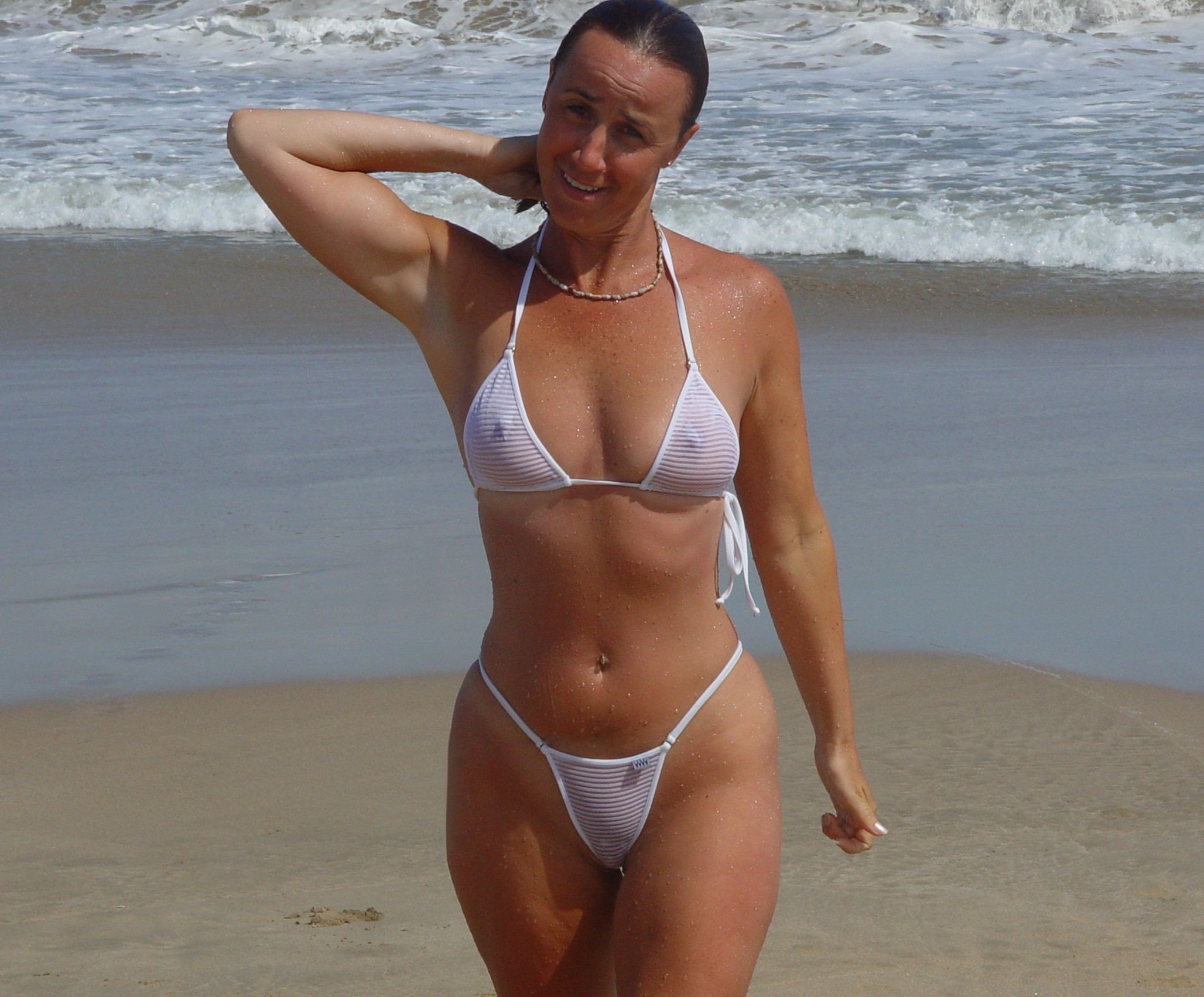 milf on the beach in a see through bikini so everyone can see her pussy and tits.