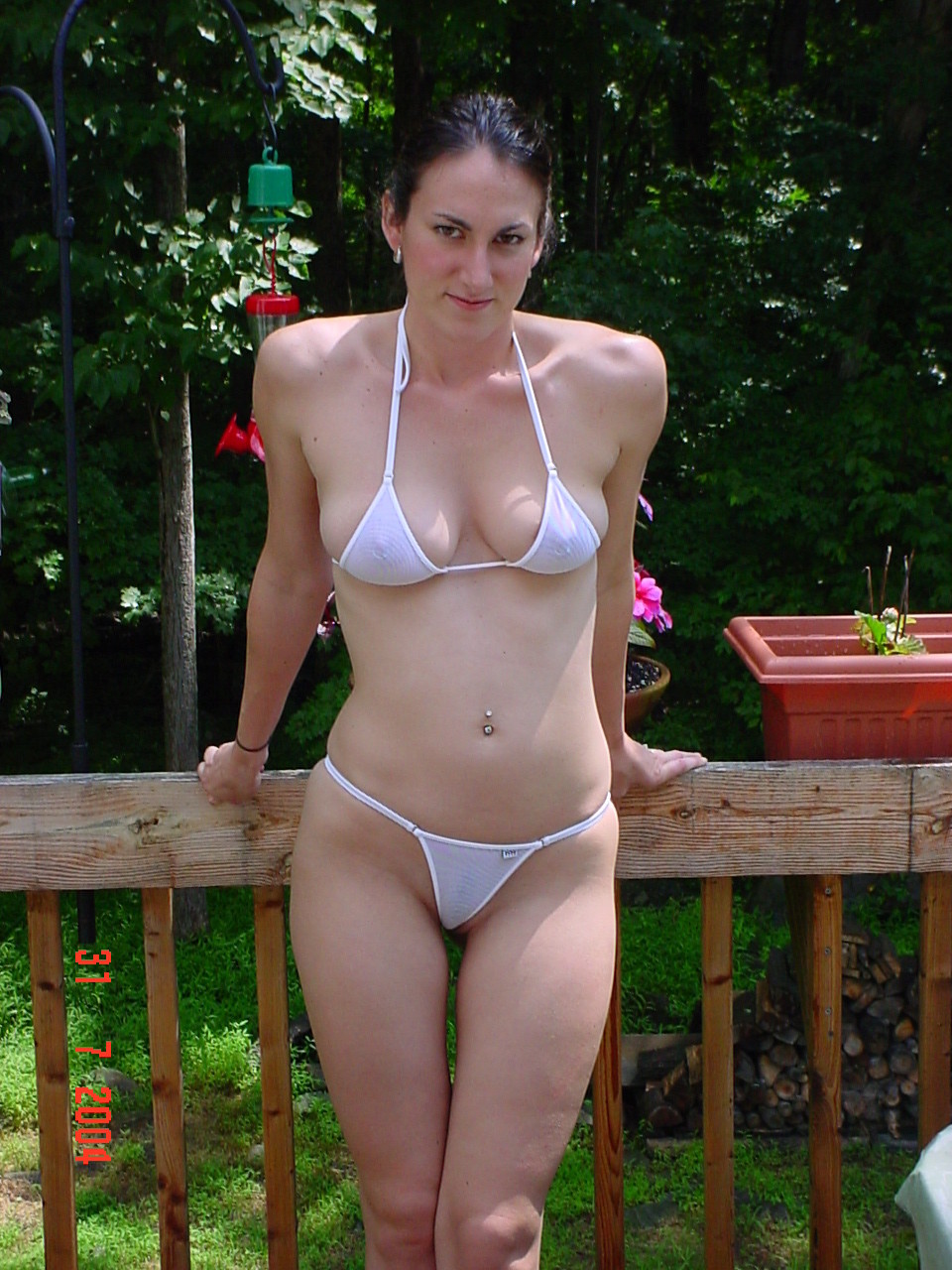 girl in backyard exposing herself in a seethrough bikini