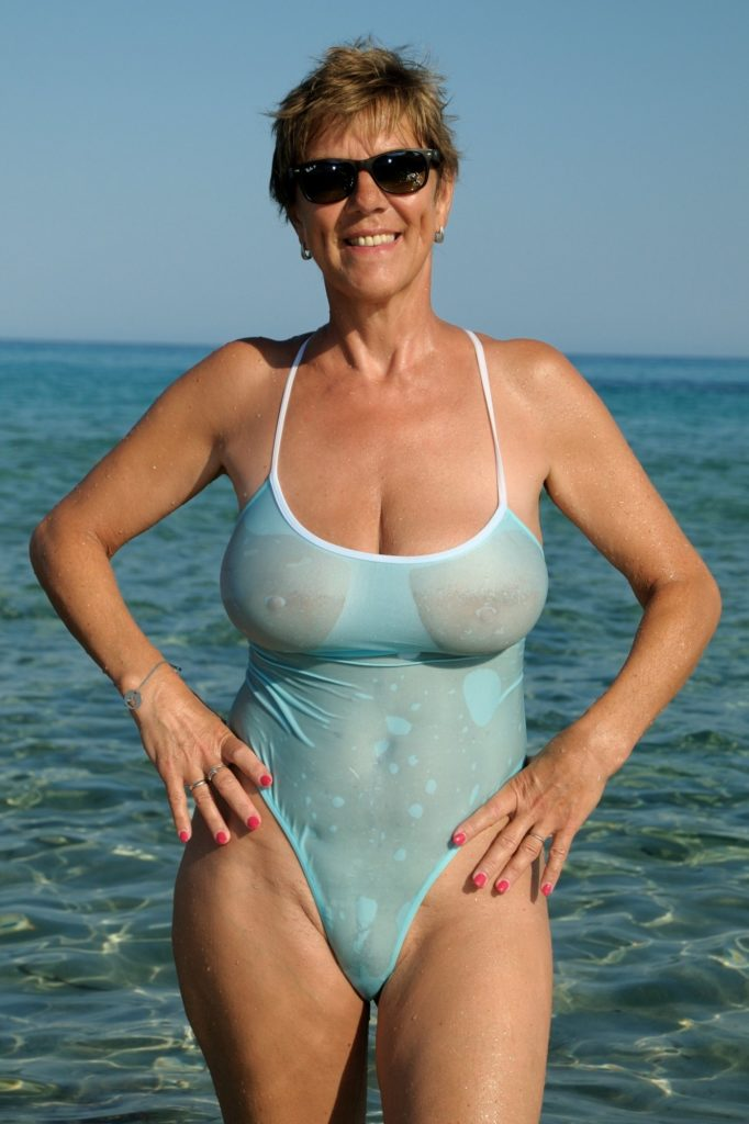 big tits milf in see through one piece at the beach