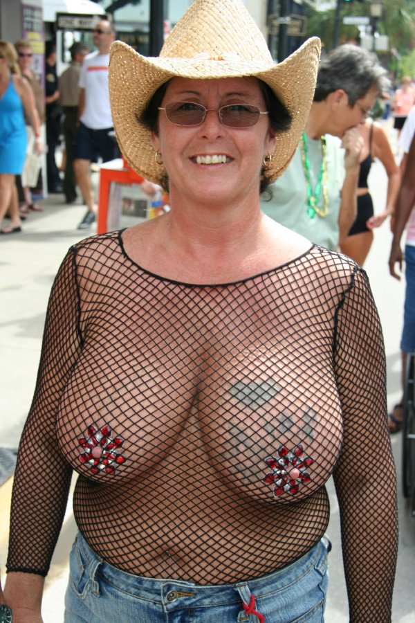 gmilf with some heafty hangers in a see through shirt on a public street