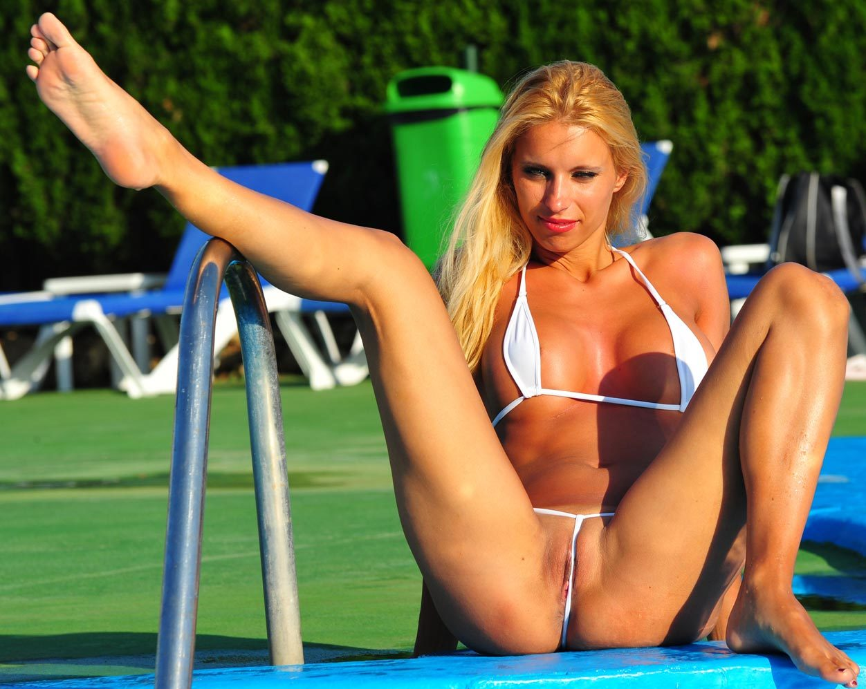 girl spread eagle at the pool with pussy floss.